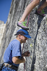 A rock climber using his partners head as a foothold.