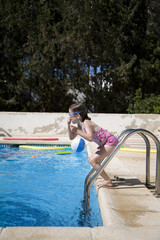 Girl about to jump into a swimming pool holding her nose