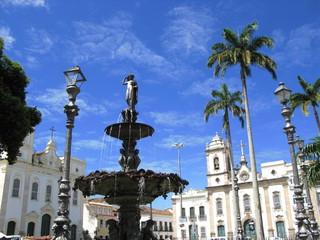 Fontaine, cocotiers et église sur une place de Bahia, Brésil