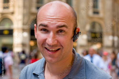 smiling man with headset in busy mall