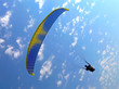 paraglide (parachute) flying under blue cloudy sky