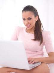 Young pretty women on couch relaxing and using laptop