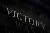 A closeup of the word VICTORY engraved on a war memorial. poster