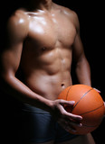 hunky asian basketball player in trunks with a ball