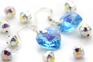 A pair of earrings puts together with shinny jewelry.