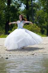 Bride on a sandy beach turns round itself