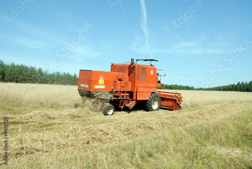 Poster red combine harvester harvesting a grain field