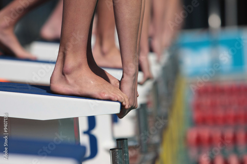 Divers on starting block ready to swim in gala
