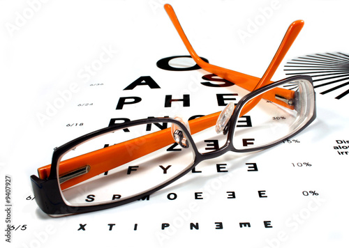 Leinwandbild Motiv Reading glasses on eye chart