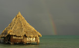 Rainbow, beach hut and sea converge