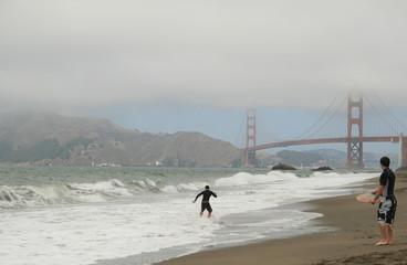 Two surfers against the Golden Gate Bridge