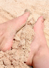 foot in gold dust on the beach