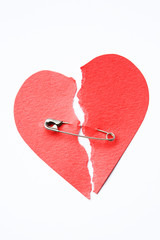 Red paper heart joined with safety pin