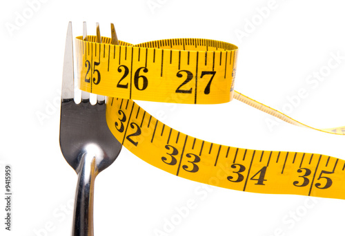 A tailor's measuring tape on a dinner fork. - 9415959