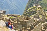 Couple admiring Inca sanctuary of Machupicchu. Cusco, Peru poster