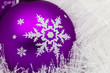 Purple glass ball on white shiny garland