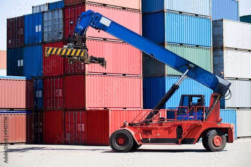 containers stacked in port with container handler / forklift