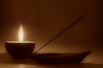 Still life with candle and incense stick, sepia toned