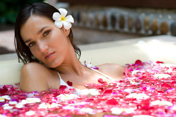 A young woman in a bath full of flowers