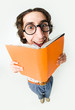Portrait of smiling male in glasses reading interesting book