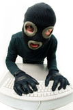 Criminal in balaclava pressing buttons of keyboard