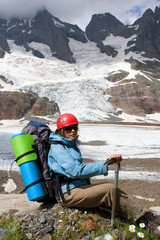 mountaineer woman with ice-axe and backpack in high mountains