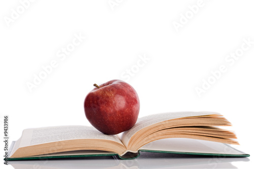 Red apple with open book and reflection on the floor