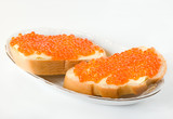 Two sandwiches with salmon roe on porcelain dish poster