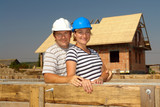 Couple wearing hard hats posing over unfinished house poster