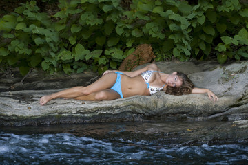 A beautiful girl laying on rocks by a mountain stream