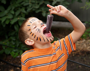 young boy with tiger face paint eating a frozen ice treat
