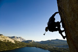 A rock climber desperately clinging to a rock face. poster
