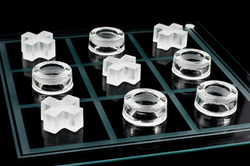 Glass tic-tac-toe game on black background