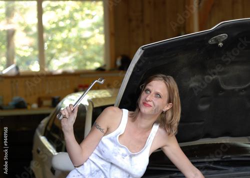 Blondine als Automechanikerin mit Schraubenschlüssel