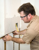 Electrician installing wiring in an insulated wall. poster