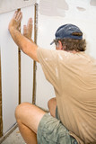 Contractor installing styrofoam insulation in a section of wall poster