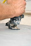 Closeup view of a contractor using a spiral saw to cut drywall poster