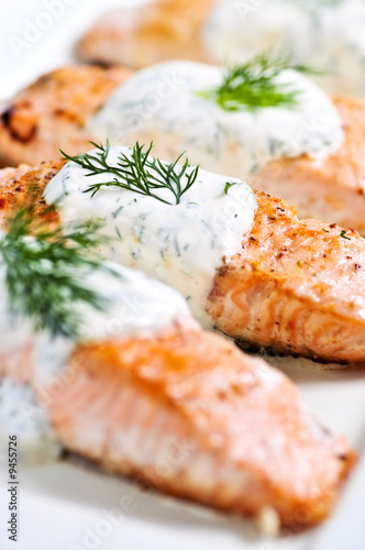 Cooked salmon fillets with dill sauce on white plate - 9455726