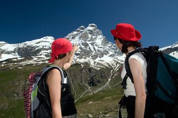 Two women with rucksacks looking at Matterhorn (Italian Alps)