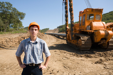 young engineer on a working site on stacking a new oil pipe