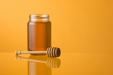 Honey jar and dipper with reflection