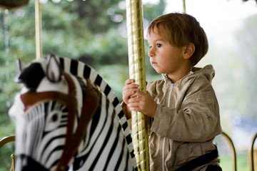 Little beauty boy on merry-go-round (on black-white zebra)