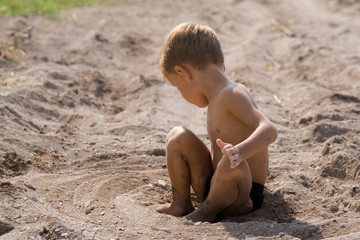 little boy sitting on sand