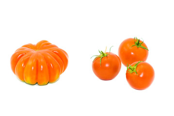Round small and big red tomatoes on a white background