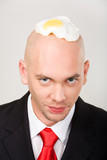 Bald man with fried eggs on top of head looking at camera