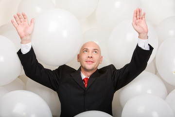 Joyful man wearing suit inside balloons raising his arms