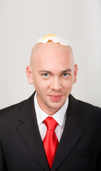 Portrait of smiling male with omelet on top of bald head