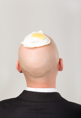 Rear view of male's bald head with fried eggs on it