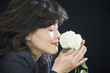 Businesswoman smelling rose