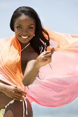 Beautiful girl having fun at the beach waving